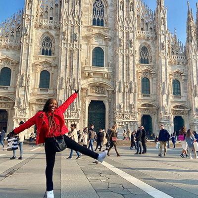 A student poses in front of the Duomo in Milan.