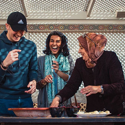 Two students in Morocco preparing a dish with a local woman