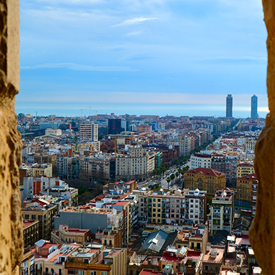 Look from a window above the city of Barcelona and blue sky in horizon