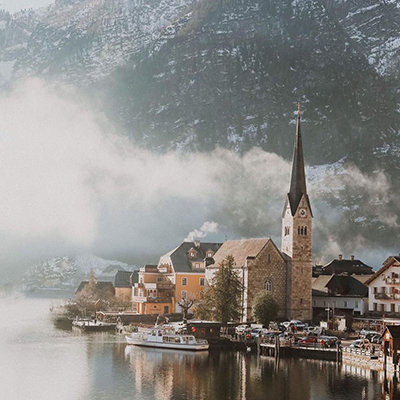A misty photo of the old buildings in Hallstatt, Austria on the water with mountains and forest in the background.