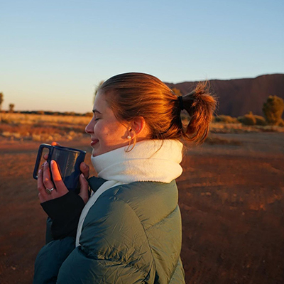 Student holding a mug close to her face in the Australian Outback