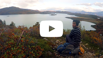 Video clip of a student sitting on a hill overlooking a lake