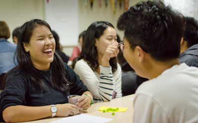 two students talking across a table laughing