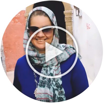 Rabat host mom outside, smiling, wearing sunglasses and a scarf. Video play button overlays the image to indicate it's clickable.