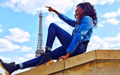 student sitting posing with arm reached out as if touching top of eiffel tower