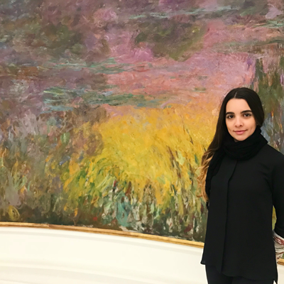 student wearing all black in front of a colorful painting