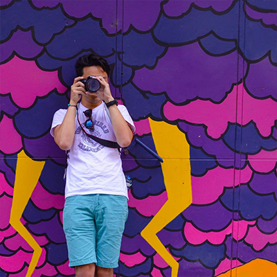 Student with camera against purple street art