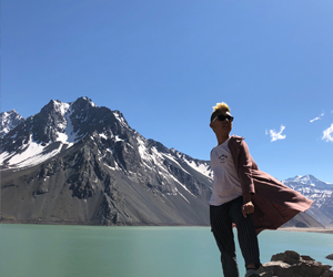Student standing in front of a mountain by a lake