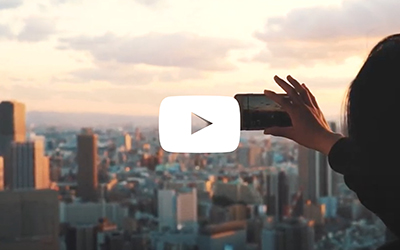 Video still with play button of person taking photo of skyline with phone