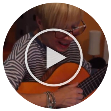 Host mom singing and playing guitar. Video play button overlays the image to indicate it's clickable.