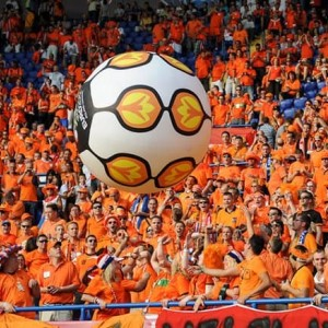 Large soccer ball being passed by a crowd in a stadium all wearing orange
