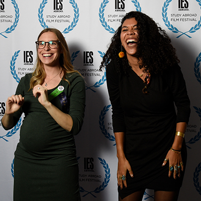 festival attendees laughing in front of IES Abroad step and repeat