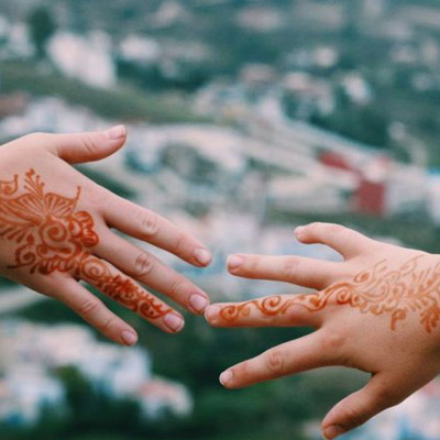 Two hands with henna art on them reaching out to each other.