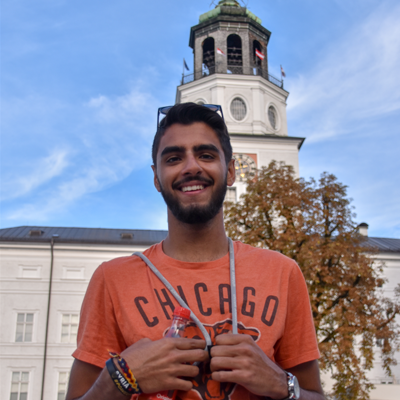 smiling student in front of a landmark in vienna in an orange shirt