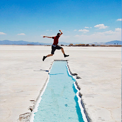 Student jumping over a stream in salt flats