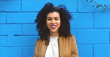 Photo of Kiah in front of a blue-brick wall in a tan jacket and white tshirt