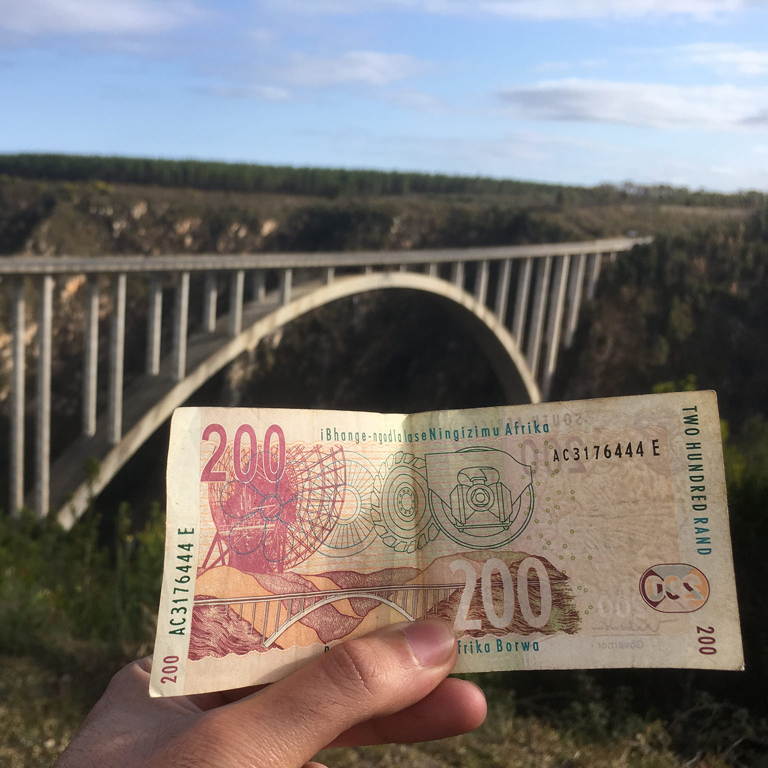 student holding money in front of a bridge