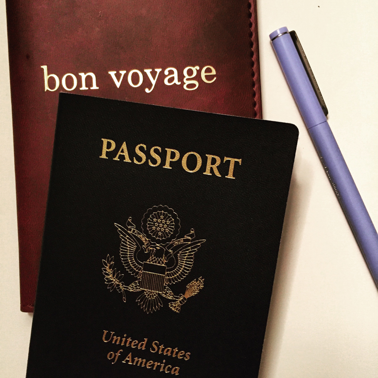 "passport on top of a sign reading ""bon voyage"""