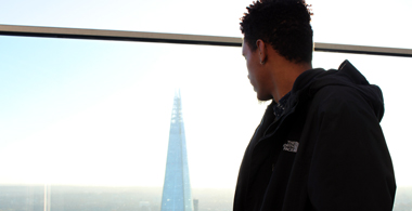 Male student looking out over London skyline and Shard