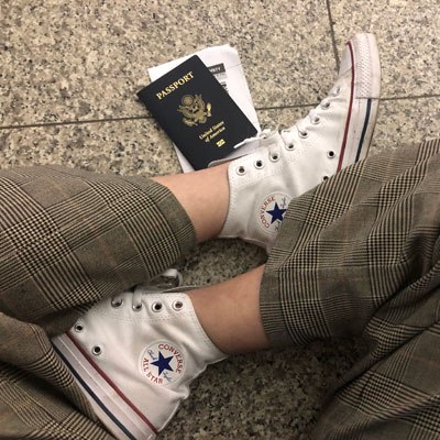 crossed legs with white sneakers and a passport on the floor