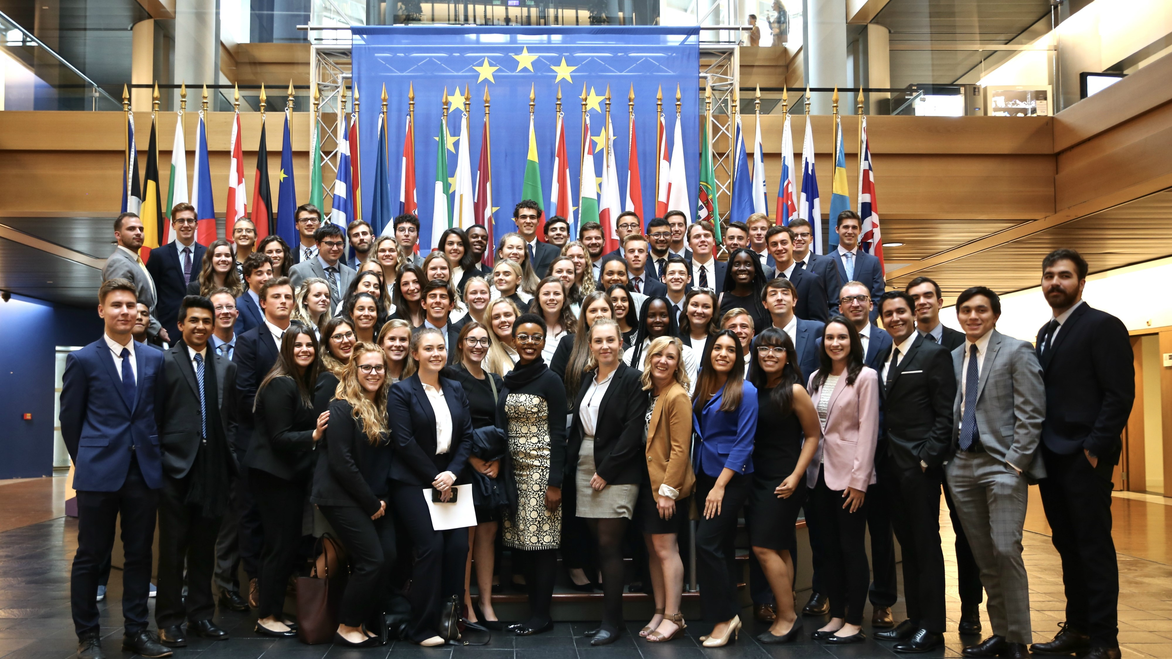 a group of students in business attire in front of world flags