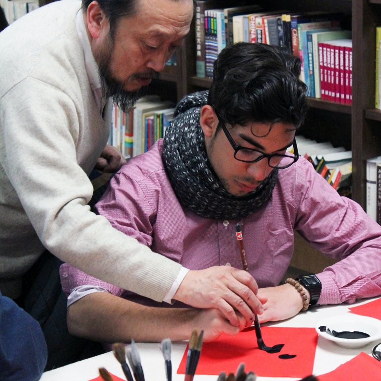 teacher helps student with calligraphy