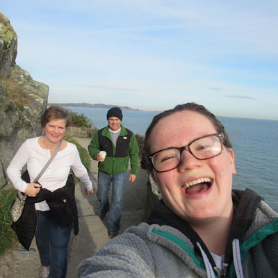 smiling girl with glasses and parents walking behind her along irish seaside