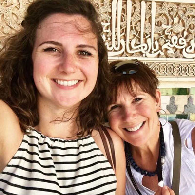 mother and daughter smiling in front of arabic wall