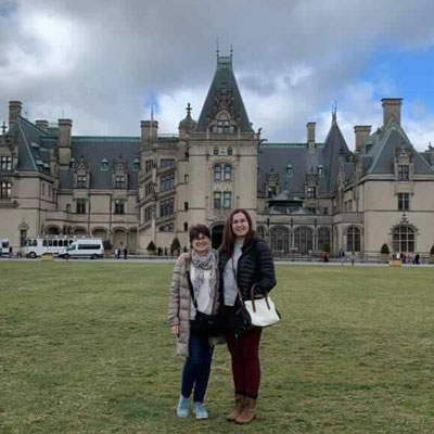 mother and daughter posing in front of large estate
