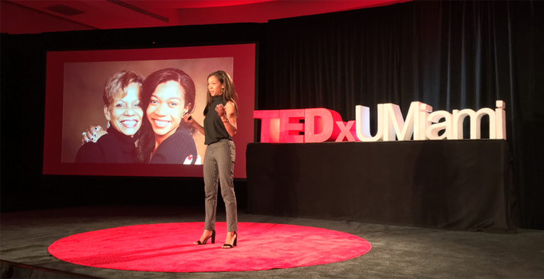 Global Citizen of the Year Breana on stage at TEDxUMiami with photo of her mother and her on the screen behind her