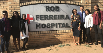 six student interns standing in front of sign for Rob Ferreira Hospital in Cape Town