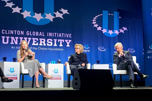 clinton family talking on stage with a blue background