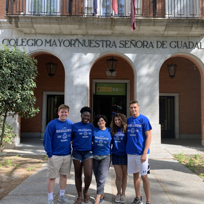 5 Madrid Study Abroad Students in Blue T-Shirts standing outside of an academic building with a Spanish name