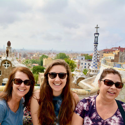 three women smiling with sunny view of barcelona in background