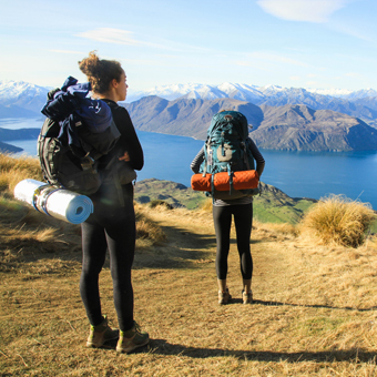students overlooking water and mountains with backpacking gear