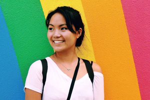 Study abroad student in front of a rainbow wall