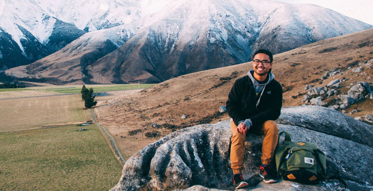marlowe padilla sitting on rocks in front of mountain landscape