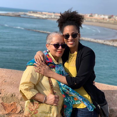 smiling mother and daughter with arms around each other in front of ocean
