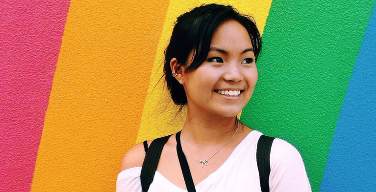 student standing in front of rainbow background