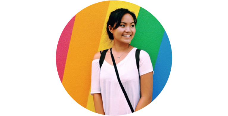 Female student in white t-shirt in front of rainbow wall