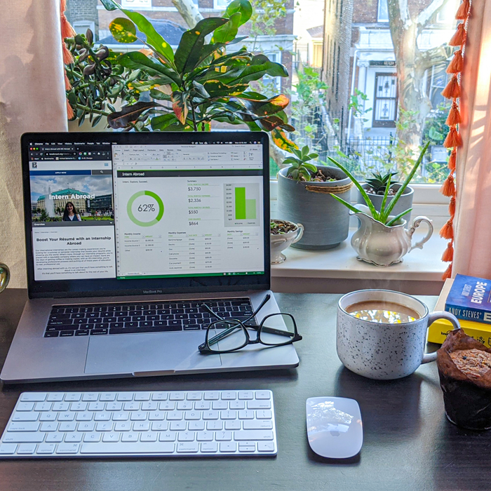 laptop open with green charts on screen and coffee and glasses on table