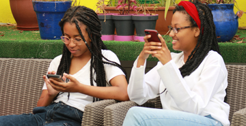 two students sitting on an outdoor couch on their phones