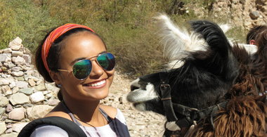 student poses with an alpaca