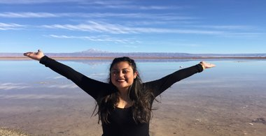 Yesenia poses with arms wide open in front of water
