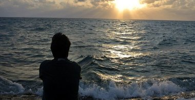 student stares at sunset over water