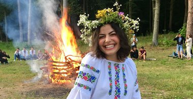 Kathleen Blehl with flower crown on her head in front of a bonfire