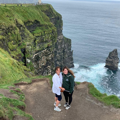 distant photo of mother and daughter standing along green seaside cliffs