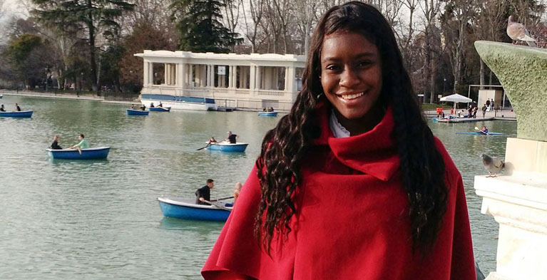 global citizen of the year sydni williams in red top standing in front of pond with boats