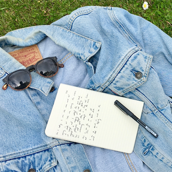Journal, pen, and sunglasses on denim jacket in grass