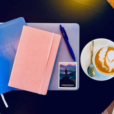 birds eye view of a desk with laptop, notebooks, and coffee